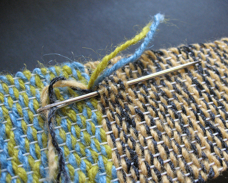 Using a tapestry needle to pick apart weaving
