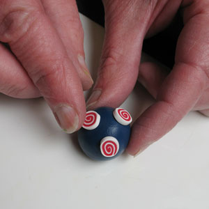 Decorating the ball of polymer clay with the Cane Slices
