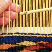 Warp being woven into weft on a tapestry